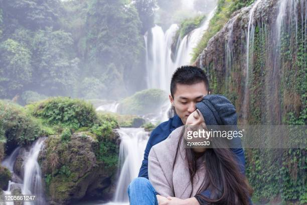 a young couple in front of a landscape and waterfall - korean ethnicity stock pictures, royalty-free photos & images