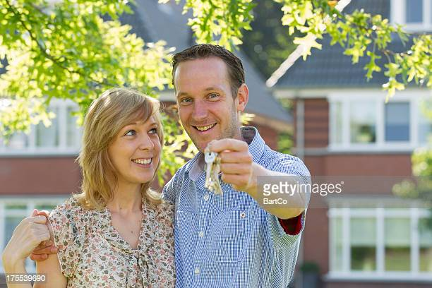 Young couple in front of house.