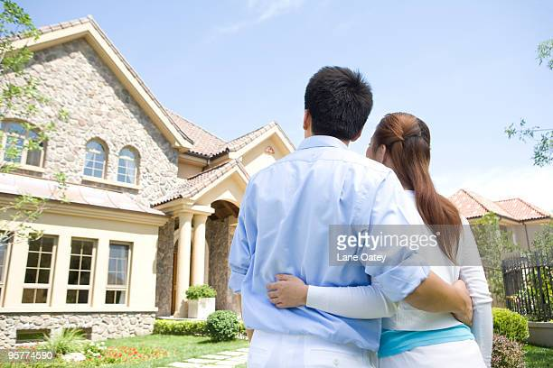 Young couple in front of house