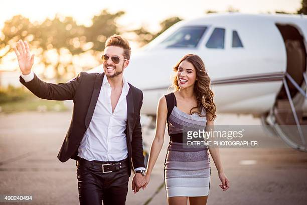 Young couple in front of private jet airplane