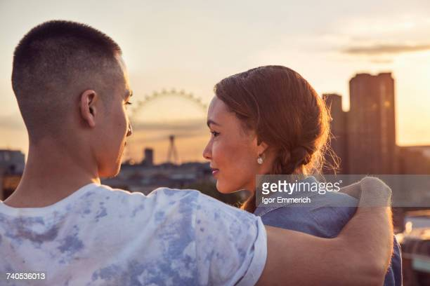 Young couple in front of skyline at sunset roof party in London, UK