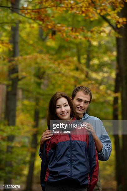 Young couple in hiking clothes standing in forest