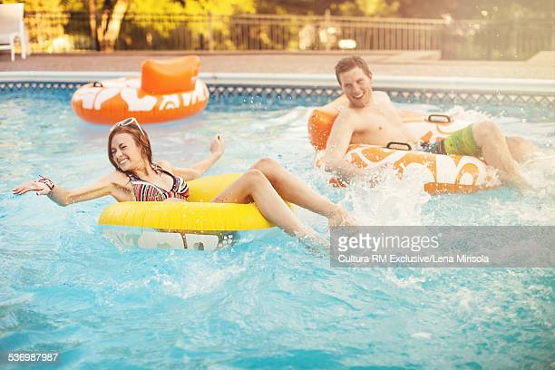 Young couple in inflatable loungers at pool party