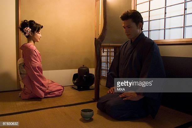 Young couple in kimono having tea ceremony
