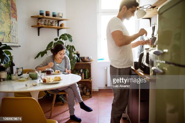 young couple in kitchen in morning - wochenendaktivität stock-fotos und bilder