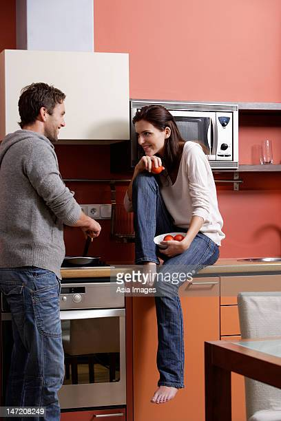 young couple in kitchen laughing and cooking together