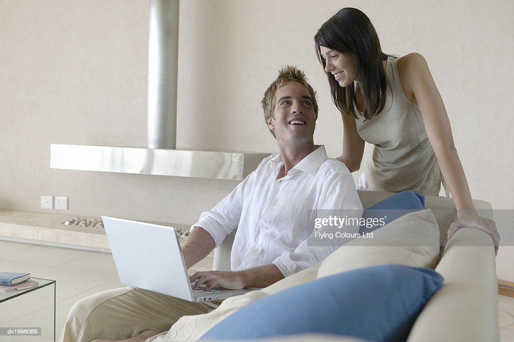 Young couple in livingroom, woman looking over man's shoulder at laptop : Stock Photo