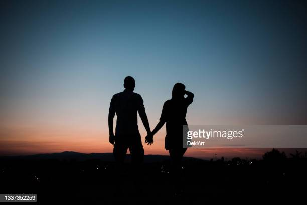 young couple in love holding hands and watching sunset - fiancé stock pictures, royalty-free photos & images