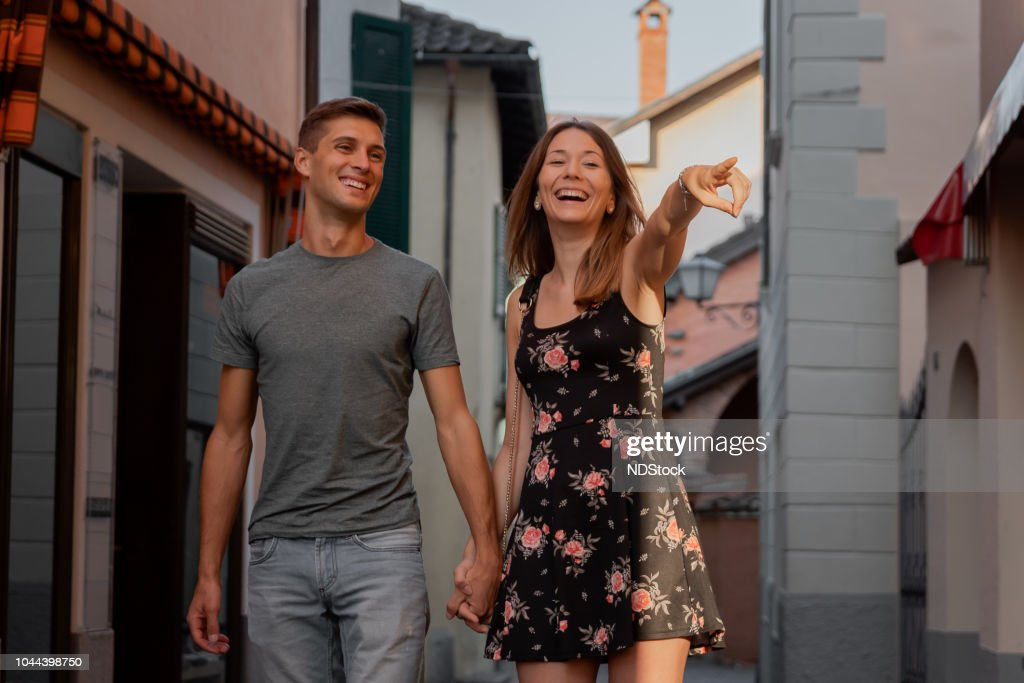 young couple in love looking at shop window in an alley in ascona during sunset : Stock Photo