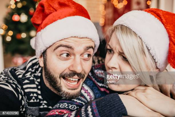 Young couple in love making selfie in front of a Christmas tree