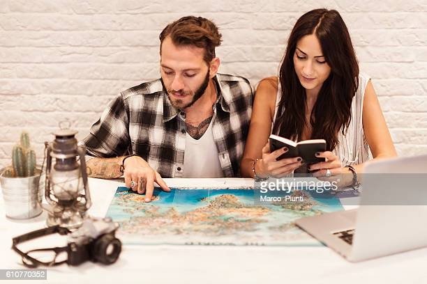 young couple in love planning a trip - pointing at camera stock photos and pictures