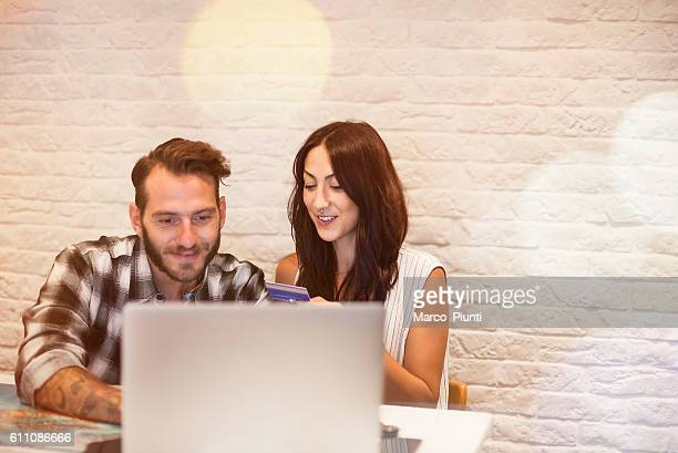 young couple in love planning a trip with laptop - making a reservation fotografías e imágenes de stock