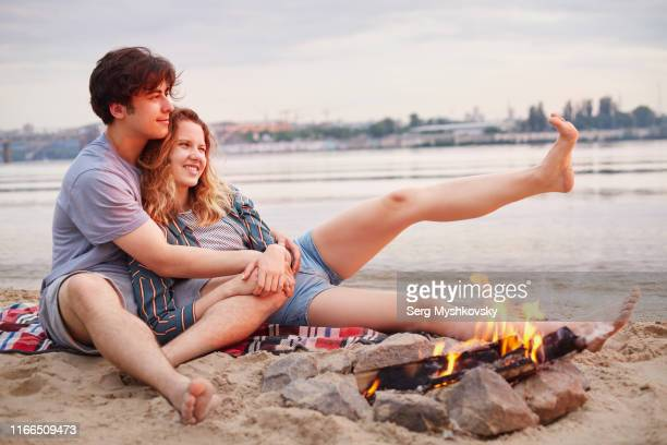 young couple in love resting near a fire on the river - myshkovsky stock photos and pictures