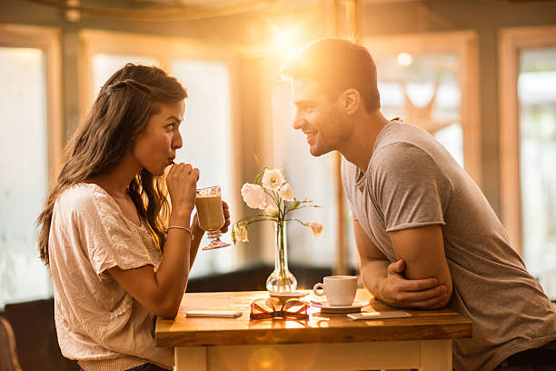 young couple in love spending time together in a cafe. - couples romance stock pictures, royalty-free photos & images