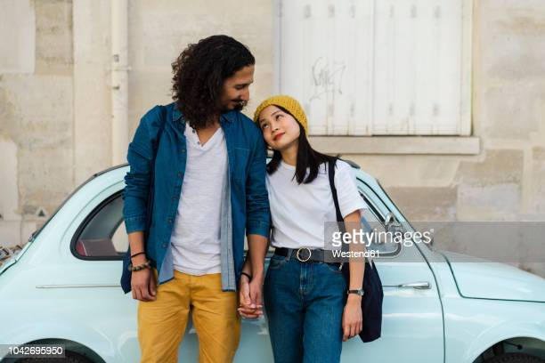young couple in love standing at small car - young couple stock pictures, royalty-free photos & images