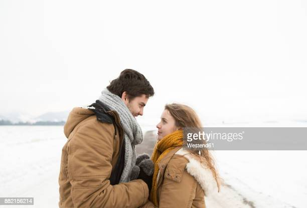 Young couple in love standing face to face on country road in snow-covered landscape