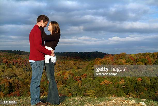 young couple in love standing on a ridge in autumn - love at first sight stock pictures, royalty-free photos & images
