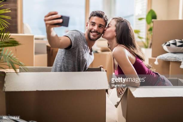 Jeune couple amoureux prenant un selfie à leur nouvel appartement.