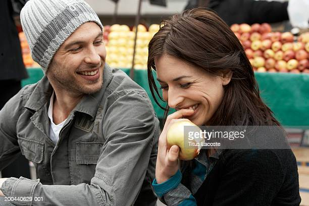 Young couple in market, woman eating apple, smiling