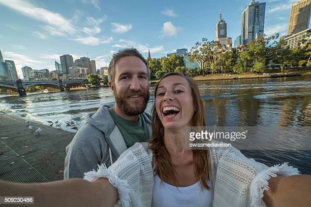 Young couple in Melbourne take selfie portrait along Yarra River