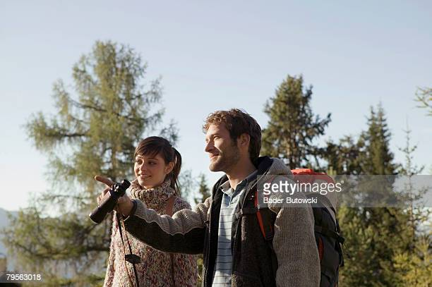 'Young couple in mountains, man holding binocular'