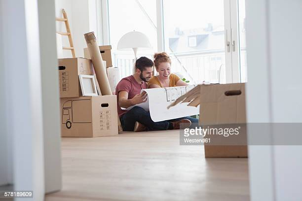 Young couple in new flat with cardboard boxes holding ground plan