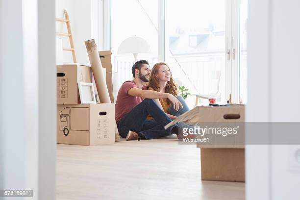 young couple in new flat with cardboard boxes - coppia di giovani foto e immagini stock