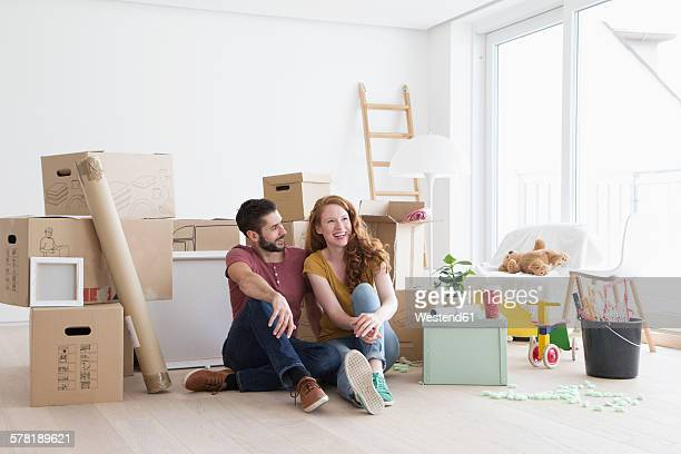 Young couple in new flat with cardboard boxes, sitting on floor