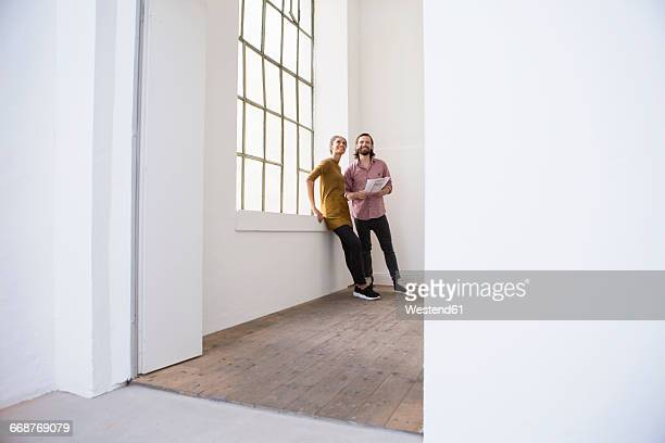 Young couple in new home looking around