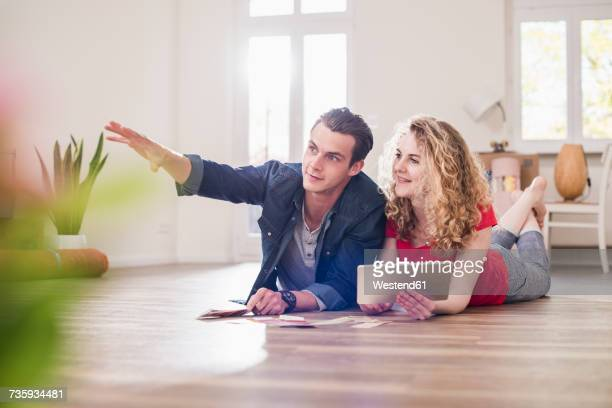 Young couple in new home lying on floor with tablet choosing from color sample