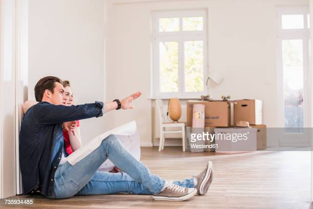 Young couple in new home sitting on floor discussing ground plan