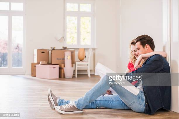 Young couple in new home sitting on floor looking at ground plan