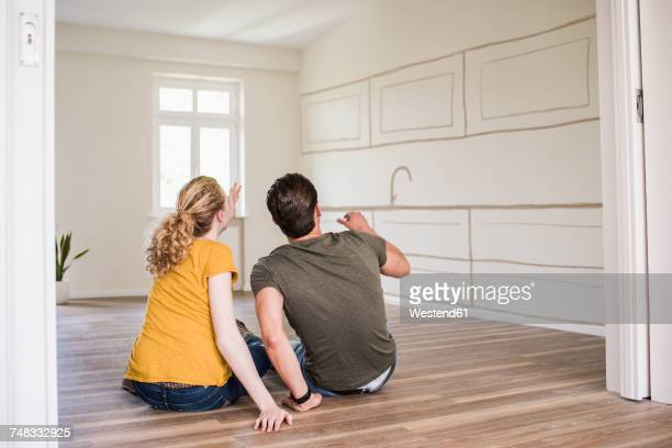 Young couple in new home sitting on floor thinking about interior design