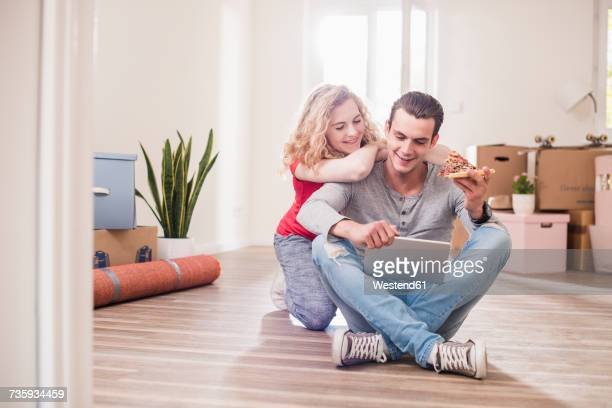 Young couple in new home sitting on floor with tablet