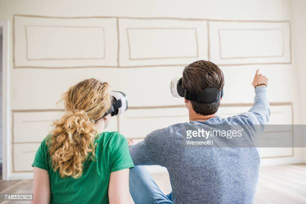 Young couple in new home wearing VR glasses thinking about interior design