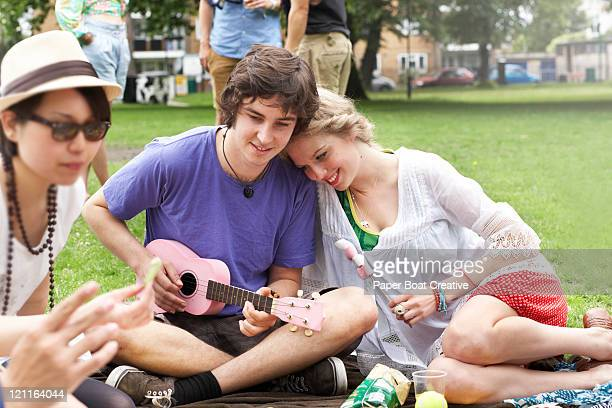 young couple in park playing ukelele - ukulele stock pictures, royalty-free photos & images