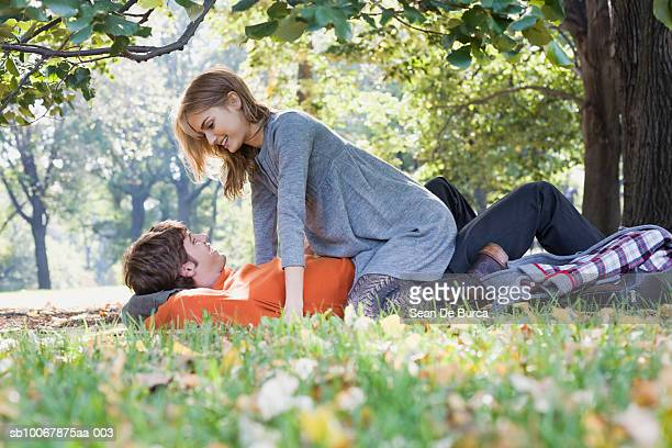 young couple in park, smiling - beautiful dominant women stock pictures, royalty-free photos & images