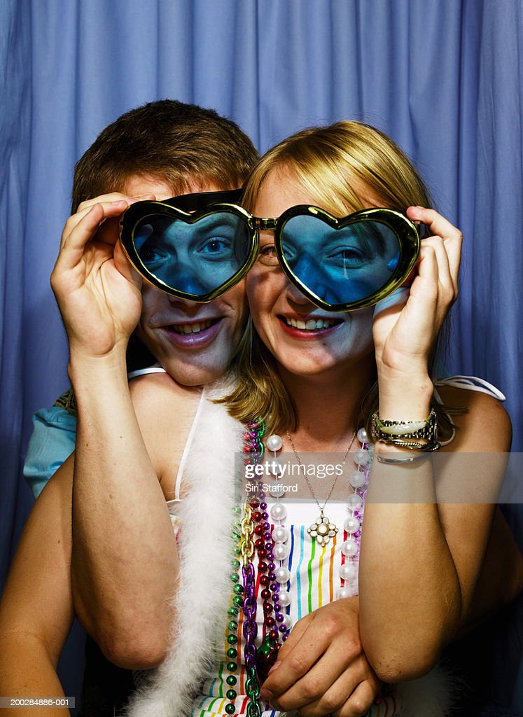 Young couple in photo booth, woman holding heart shaped glasses : Stock Photo