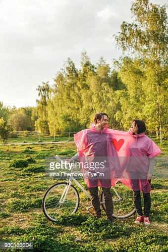 Young Couple In Pink Raincoat Standing With Bicycle On Field Against Sky
