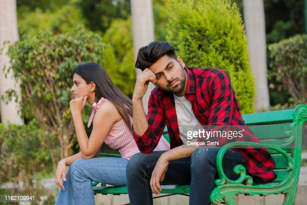 young couple in public park - stock photo - bonding stock pictures, royalty-free photos & images
