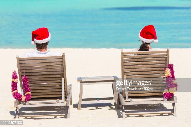 young couple in santa hats relaxing on tropical beach during christmas vacation - caribbean christmas stock pictures, royalty-free photos & images