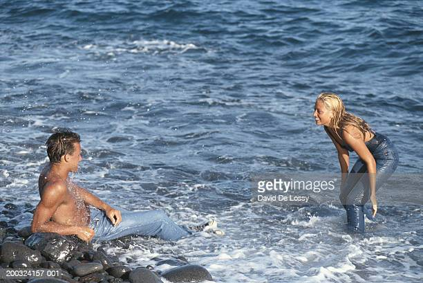 young couple in sea, smiling - wet jeans stock photos and pictures