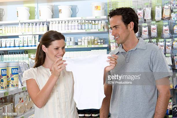 Young couple in shop, woman holding baby clothes