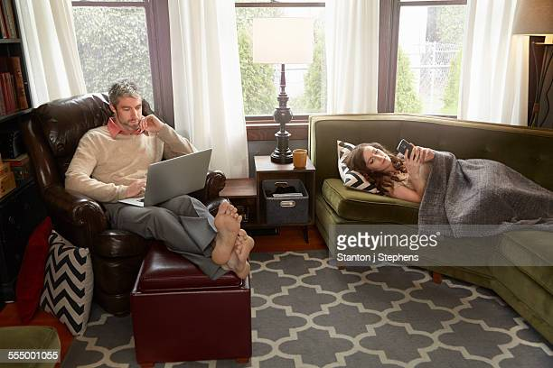 Young couple in sitting room using smartphone and laptop