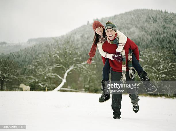 Young couple in snow, man giving woman piggy back, smiling, portrait