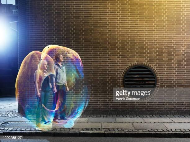young couple in soapbubbles - relationship stockfoto's en -beelden