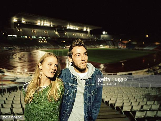 Young couple in sports stadium, night