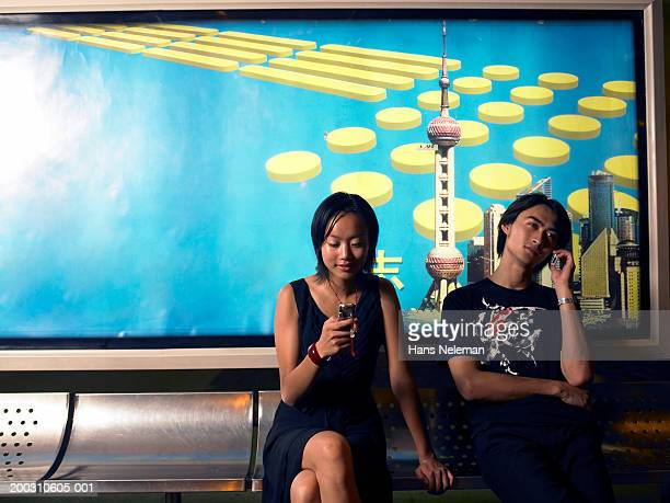 young couple in station using mobile phones - shanghai billboard stock pictures, royalty-free photos & images