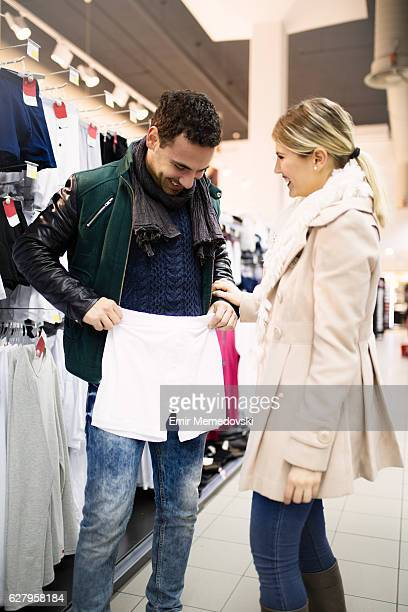 young couple in store buying  men's underwear - frau in slip stock-fotos und bilder