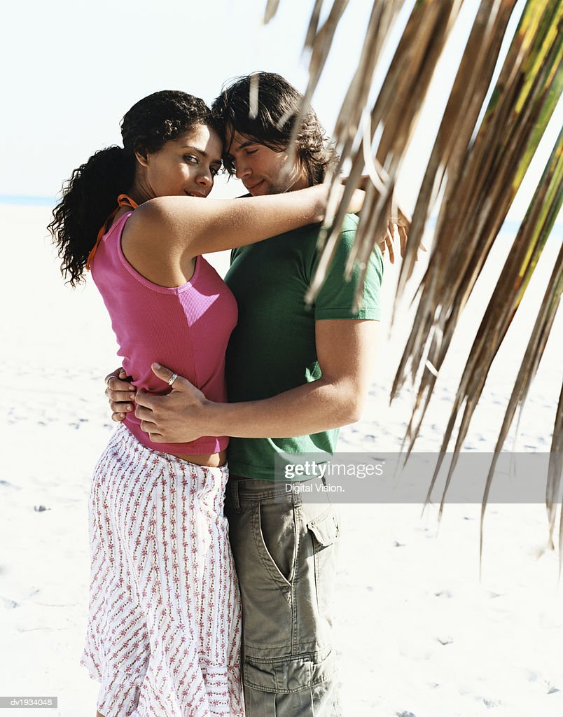 Young Couple in Summer Clothing Stand on a Beach Embracing : Stock Photo